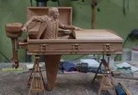 Lifesize carving of a wooden coffin which is also a boat